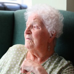 An older lady sits in a green chair and looks sadly away from the camera