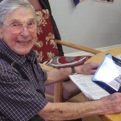 Helpful: an older gentleman smiles while holding a tablet computer