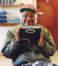 Donate - an older homeless lady smiles as she holds her new radio