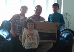 Refugee family holding their new WaveLength TV