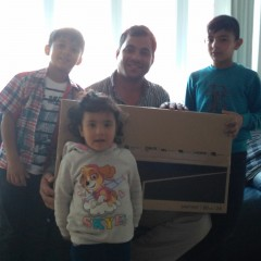 Refugee family holding their new WaveLength TV