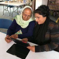 Advisory Group = Two women use a tablet computer