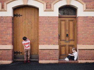 Young people - two boys stand apart against a brick wall
