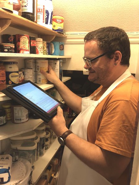 Beneficiary at Dial House using a tablet, given by WaveLength, to help find ingredients to use for recipe