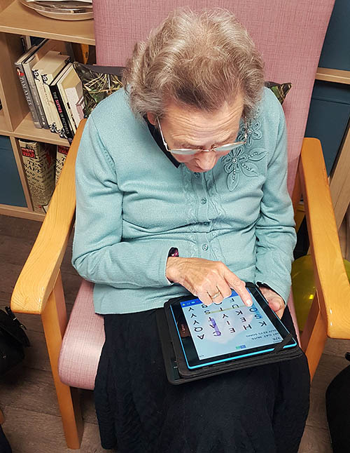 Lady using a tablet given to her by WaveLength