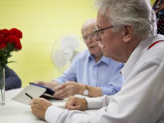 Men at Gatehouse Caring on tablets given to them by WaveLength