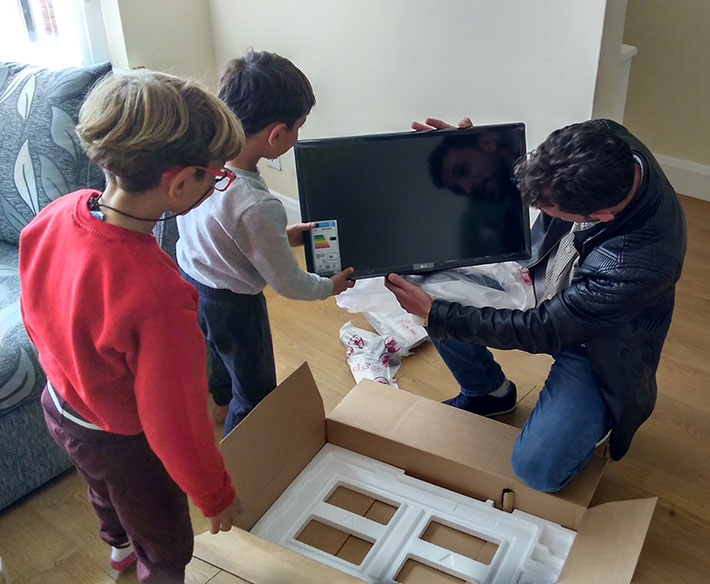 Man with sons unpacking TV