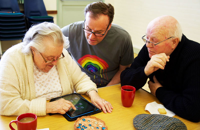 Two men and a woman using a tablet.