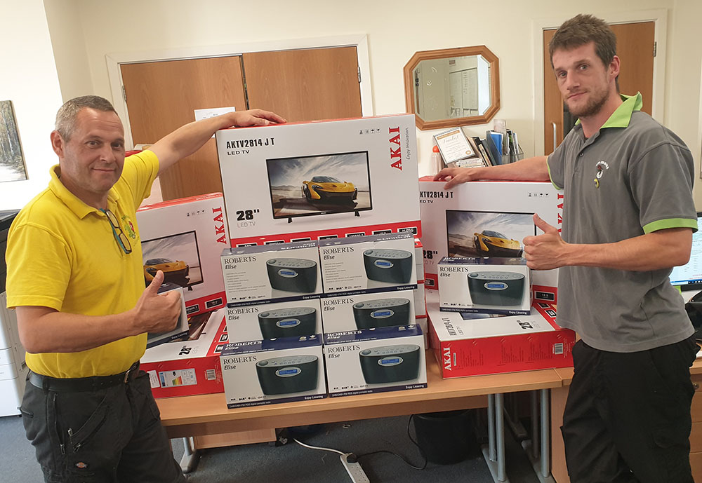 Emmaus staff with WaveLength radios and televisions